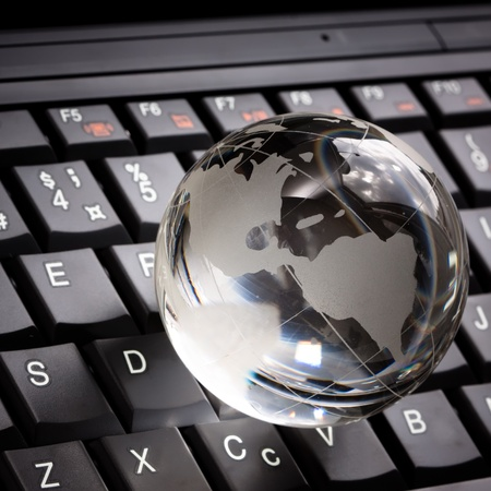 Crystal globe on laptop keyboard Stock Photo - 8863881