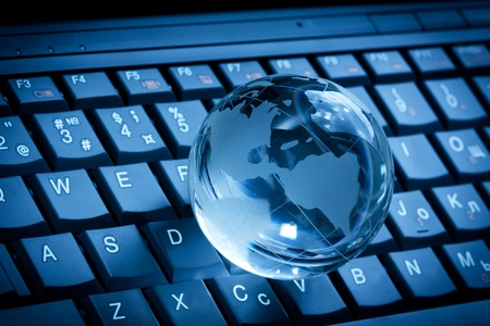 Crystal globe on laptop keyboard photo