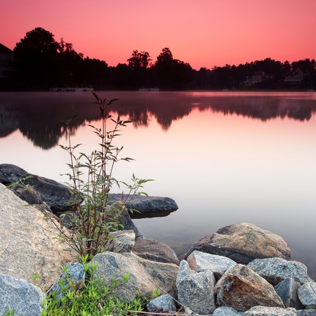 panoramic countryside view of lake and houses during sunrise Stockfoto