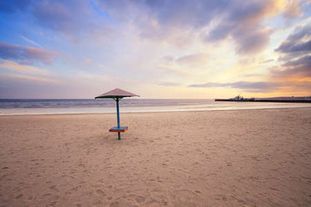 azov sea: empty beach with lonely umbrella at sunset. Azov sea, Ukraine