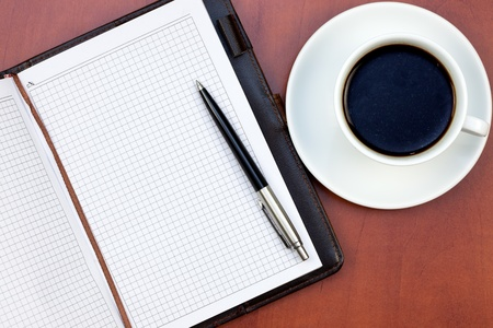 Coffee cup, notebook and pen on the office table Stock Photo - 9252807