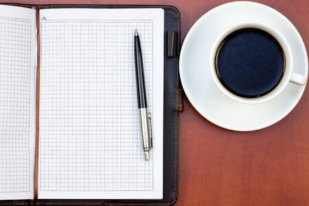 Coffee cup, notebook and pen on the office table Stock Photo - 9252811
