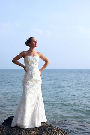 beautiful bride over blue sky and sea background  photo