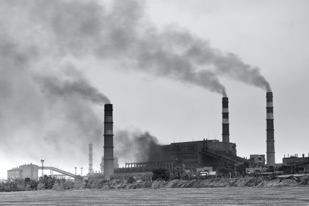 Black and white photo of plant with smoke. Air pollution photo