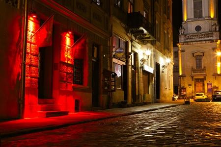 outdoor cafe: illuminated street at night. Old european city Stock Photo