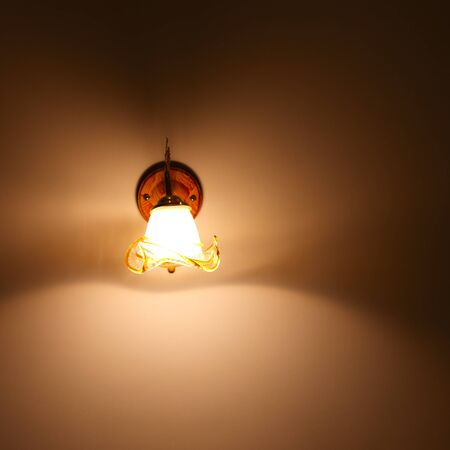 Lighted classic sconce on the wall photo