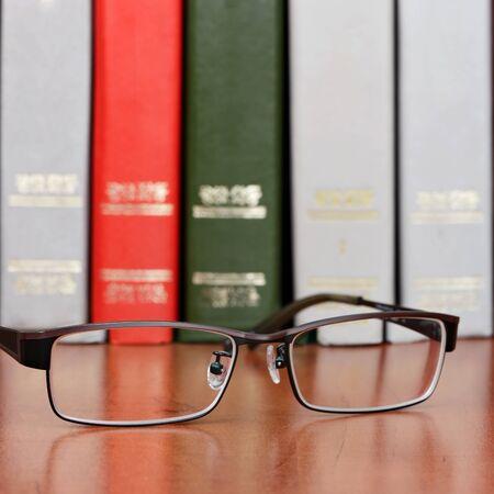 Bril op de boekenplank Stockfoto