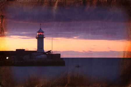 Retro picture of lighthouse before sunrise photo