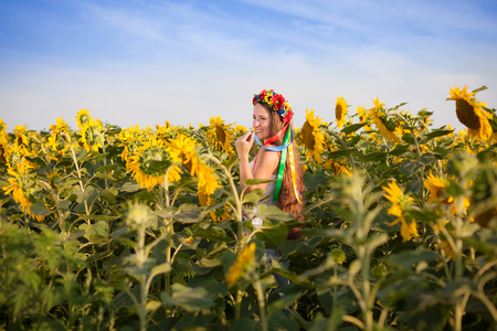 Close-up portrait of beautiful young woman at sunflower field photo