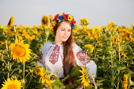 Beautiful young girl at sunflower field. Ukrainian girl photo