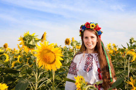 Beautiful young woman at sunflower field photo