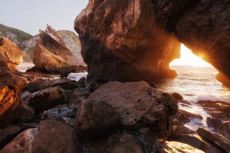 rock arch: Sunlight through rock arch, Ursa beach, Portugal Stock Photo