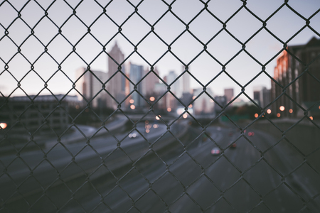 wire mesh: Grunge city skyline through the wire mesh fence. Abstract blurred cityscape background