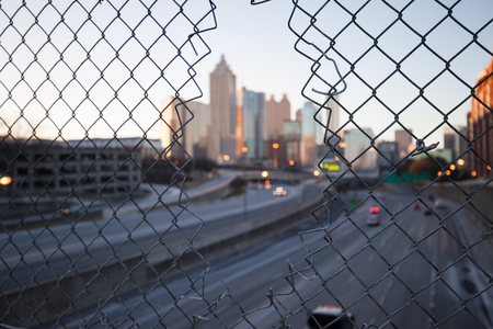 wire mesh: City skyline through the wire mesh fence. Abstract blurred cityscape background