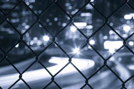 metal mesh: Nigh city bokeh lights through the wire mesh fence