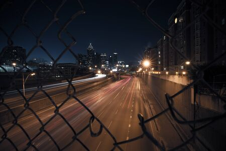 metal mesh: Night city skyline through the wire mesh fence Stock Photo