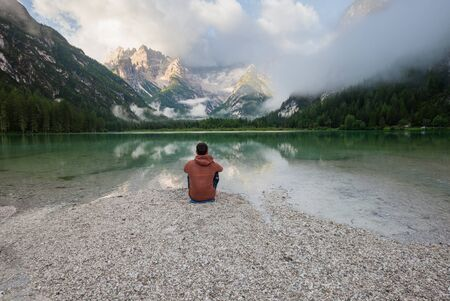 Man watching cloudy sunrise at the mountain lake