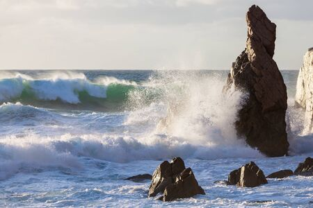 Ocean big waves crashing rocky cliffs. Stormy sunset seascape Stock Photo