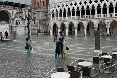 VENICE, ITALY - NOVEMBER 07, 2017: Tourists walking along flooding Piazza San Marco in Venice Imagens