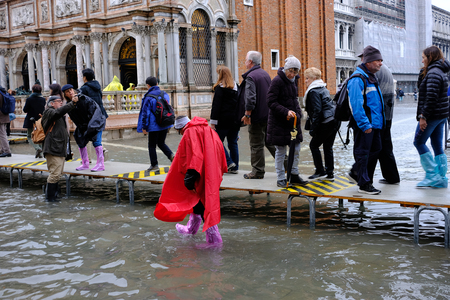 VENICE, ITALY - NOVEMBER 07, 2017: Tourists walking along flooding Piazza San Marco in Venice 스톡 콘텐츠