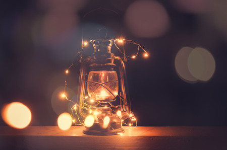 Vintage retro lantern with bokeh lights over dark background Standard-Bild