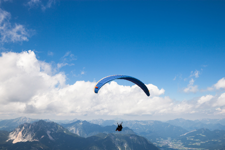 Paraglider flying on the deep blue sky