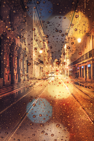 Rainy day in the city at night, traffic car and city lights on the street Banco de Imagens