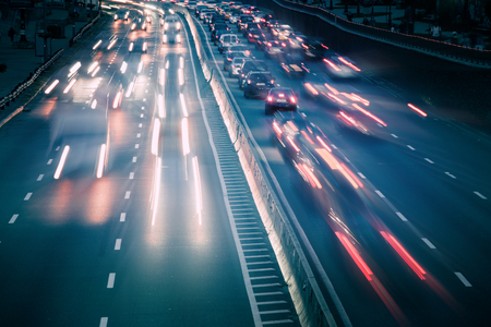 View of traffic car lights on a busy highway at night. Motion blur soft focus