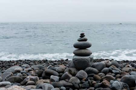 Stack of pebbles on a big rock at the beach on the ocean background 写真素材