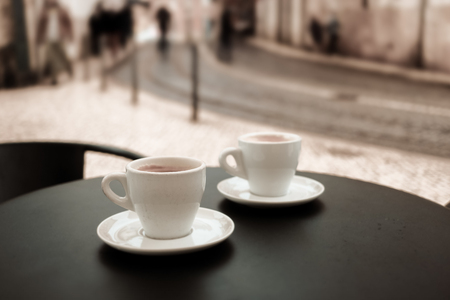 Coffee cup on table in street cafe. Vintage tone image