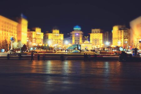 Night city street with cars on the road and walking people, tilt-shift effect. Kyiv, Ukraine 版權商用圖片