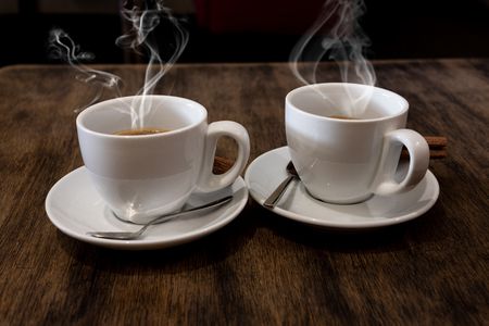 Two coffee cups on wood table in cafe interior
