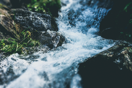 River with rocks and moss with small waterfall in the summer forest. Tilt-shift effect 写真素材