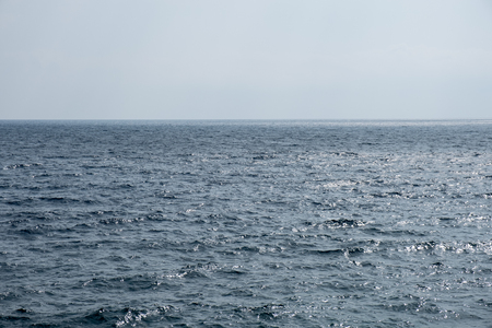 Deep blue surface of a calm sea merging with the empty sky Stock Photo