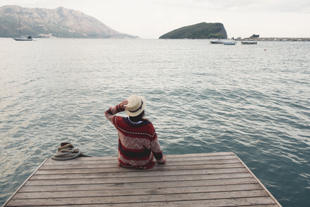 young girl in hat sitting on wooden pier and looking the horizon.