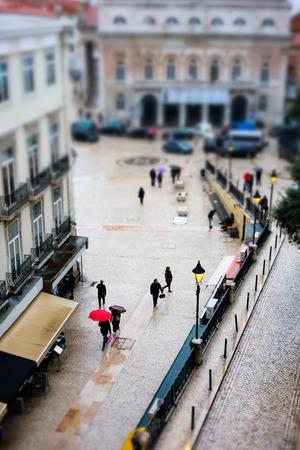 Urban landscape scene. People walking under rain. Tilt-shift effect. Lisbon, Portugal