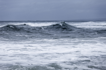 Stormy clouds and crashing ocean waves during storm in the atlantic ocean