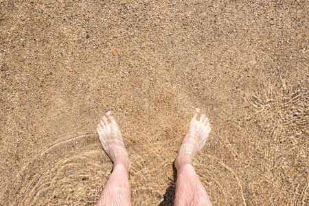 Foot on the beach. Top view of man legs on the water Stock Photo
