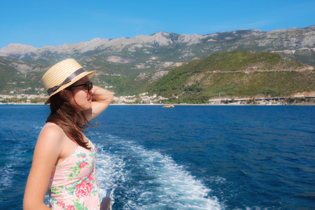 Young woman standing on the ship board and looking into the distance. Summer travel destination