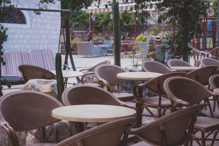 Empty coffee terrace with tables and chairs in old town of Budva, Montenegro. Vintage style photo