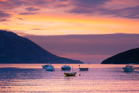 View from the city of Budva on the island of St. Nicholas. Sunrise at the sea. Sea, mountains, island and boats. Montenegro