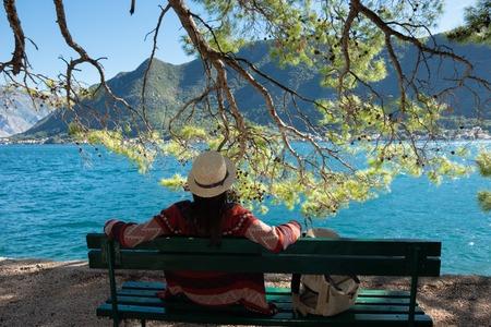 Ragazza in cappello che si siede su un molo di legno vicino all'acqua. Concetto di viaggio estivo