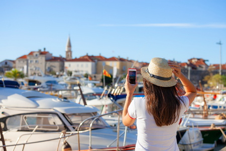 Young travelling woman in hat taking photos of summer sunny Budva landscape with smartphone camera. Brunette girl making photography on summer mediterranean destination in Montenegro Foto de archivo