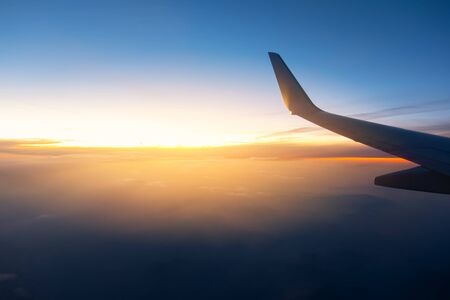 Airplane wings in the sky and a mountains view scene in the sunrise. Travel and adventure.