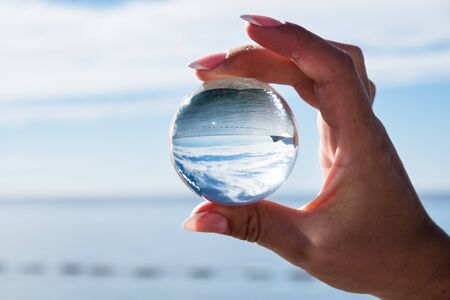 Womans hand holding a crystal ball, looking through to the ocean and sky. Creative photography, crystal ball refraction Stockfoto