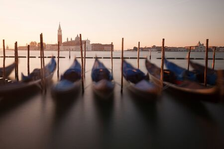 Venice classic sunrise view with gondolas on the waves. Venice, Italy