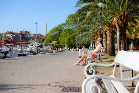 Europe summer travel mediterranean destination. Tourist woman on vacation, sitting on the bench old Mediterranean city seafront. Budva, Montenegro