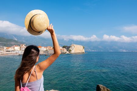 Back view of a young beautiful woman in a hat looking to the old town Budva, Montenegro. Summer vacation destination