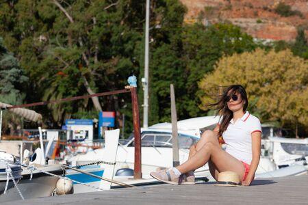 Beautiful young woman posing while sitting close to the boats at Mediterranean city marina port. Budva, Montenegro Stockfoto