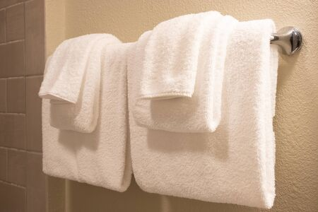 Clean white towel on a hanger prepared to use. Stock Photo